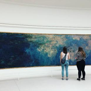 Two people standing in front of a large painting of water lilies