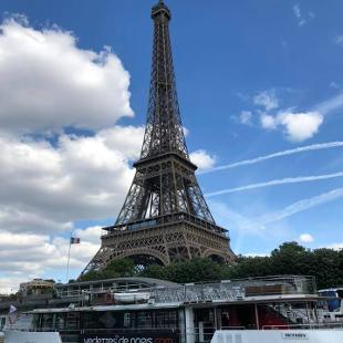 An image of the Eiffel Tower overlooking a river with a boat