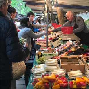 People buying food at an outdoor market