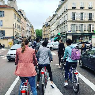 A group of people riding bikes down a street in Paris