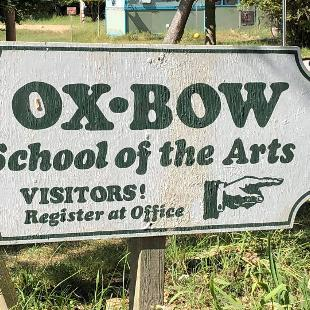 "A sign reading ""Ox-Bow School of the Arts"" and ""Visitors! Register at Office"" with a pointing hand"
