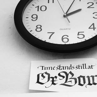 """A sign underneath a clock reading """"Time stands still at Ox-Bow"""""""