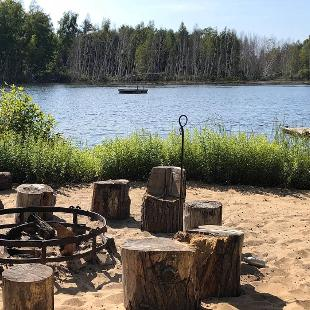 A fire pit surrounded by log stools on a beach next to a lake