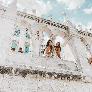 Two women leaning out of an archway smiling down at the camera