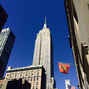 A view looking up at the Empire State Building, with other buildings around it