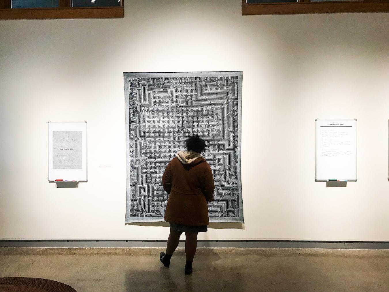 """A person standing in front of an art piece featured in the show """"Middle Grounds"""" in the De Pree Gallery."""