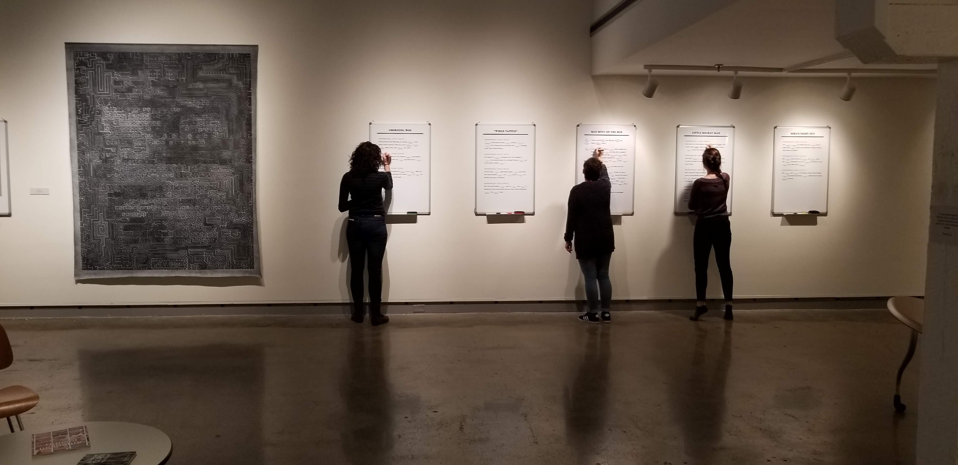 """People writing things on whiteboards featured in the show """"Middle Grounds"""" in the De Pree Gallery."""