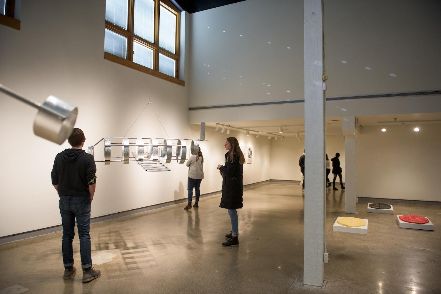 """People viewing artwork inside the De Pree Gallery during the show """"Flight."""""""