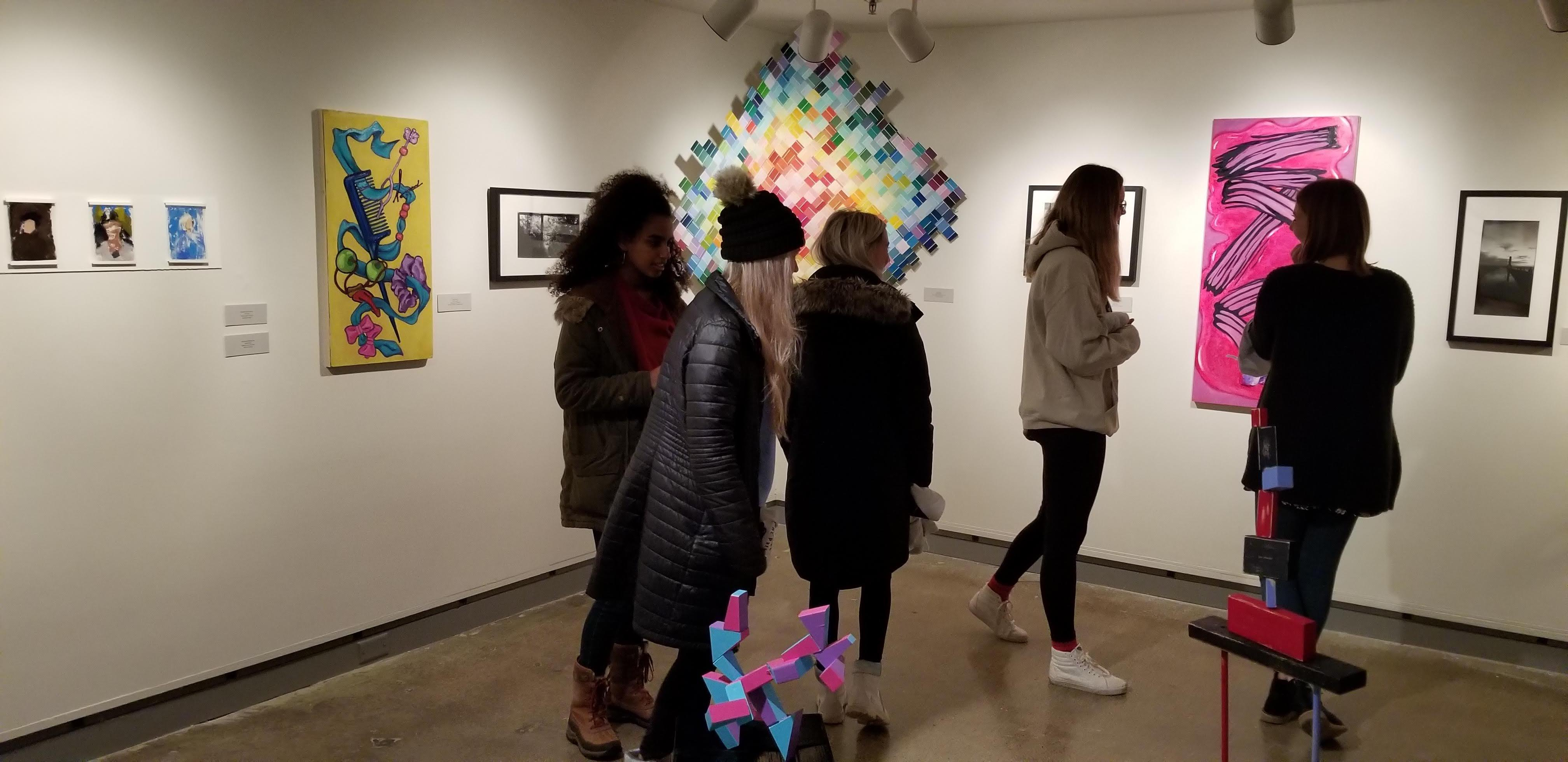 People standing around looking at art on display in the gallery during the Juried Student Show.