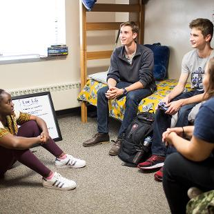 Students in a student room with bunk beds.