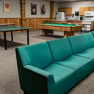 Lounge area of Scott Residence Hall with a couch, ping pong table and pool table.