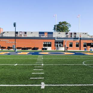 A photo of the exterioer of the Jim Heeringa Athletic Center taken from center field of the Ray and Sue Smith Stadium.