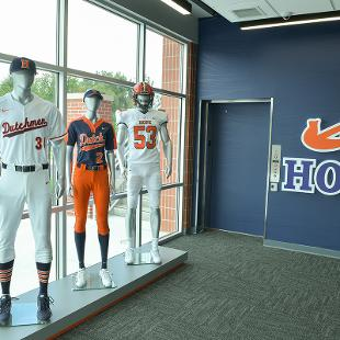 A football uniform, a softball uniform and a baseball uniform are displayed on three mannequinns inside the entryway of the Jim Heeringa Athletic Center.