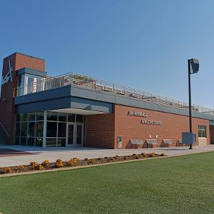 A photo of the exterioer of the Jim Heeringa Athletic Center taken from the home field side line.