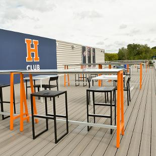 The sky desk is the open area with tables and stools where people can watch the football game.