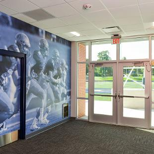 The wall art outside of the training room is an action football photo.
