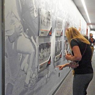 Visitors puruse the historic photo display in the hallway of the Jim Heeringa Athletic Center following the dedication.