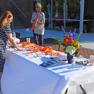 Staff sets up the welcome table prior to the dedication.