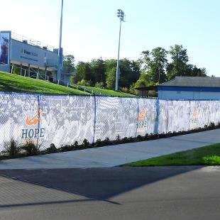 The fence surrounding the Ray and Sue Smith Stadium has screens with graphics of Hope football photos