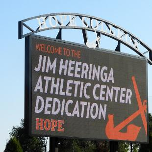 The scoreboard at the Smith Stadium displays a graphic Jim Heeringa Athletic Center Dedication. Hope with an orange anchor