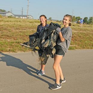 Students work on a farm collecting trash.