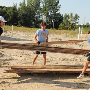Three male students move a pile of boards.
