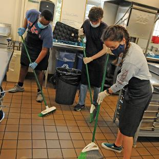 Two males and one female mop the kitchen floor at Western Seminary.