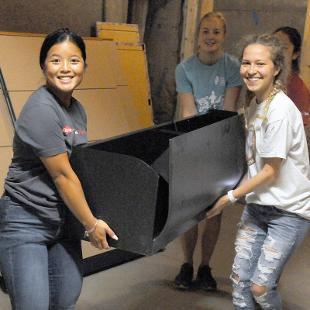 four female students move stuff.