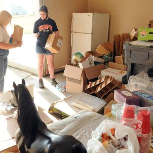one student helps organizing a garage full of odd and ends.