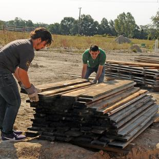 Two male students move a pile of boards.
