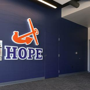 The Hope logo with the orange anchor and blue HOPE letters in the navy entry way of the  Jim Herringa Athletic Center.