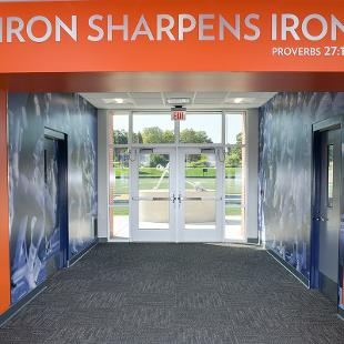 """The entry way to the hallway to the football field says """"Iron Sharpens Iron"""" Proverbs 27:17."""