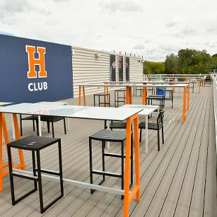 The open sky deck features an H-Club panel  on the wall as well as high top tables and stool for people to use while watching a game.