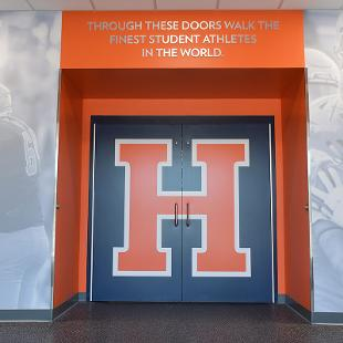 """The locker room entry doors have a huge H branded for athletes and above the doorway it states """" Through these doors walk the finest student athletes in the world."""""""