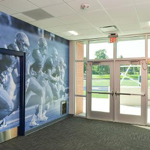 The wall outside the athletic training / rehabilitation room is a huge photography from a football game.