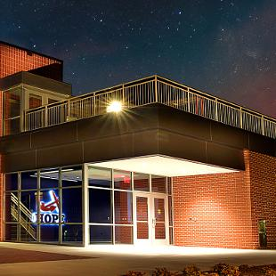 Full view of the Jim Herringa Athletic Center taken at night from west sideshowcasing the front and the entry way. The ornamental Hope Anchors on the exterior of the building and then entry way are lit up