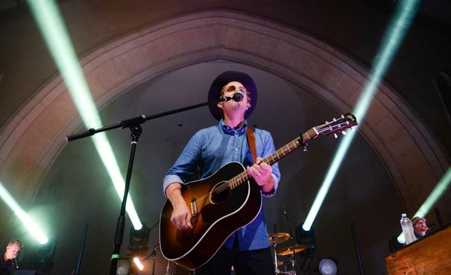 Ben Rector performing with a guitar in Dimnent Chapel