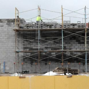 A wide-shot of the construction site with scaffolding and machinery.