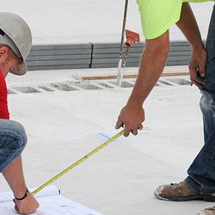Construction workers examining the base of the building.