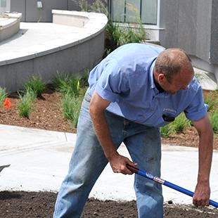 People doing landscaping work in front of the building.