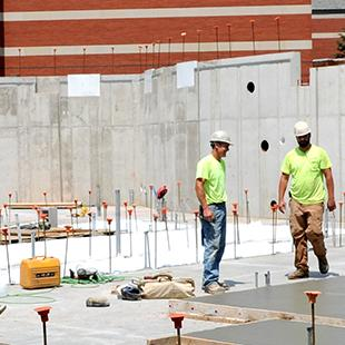 Workers at construction site with the Martha Miller Center in the background.