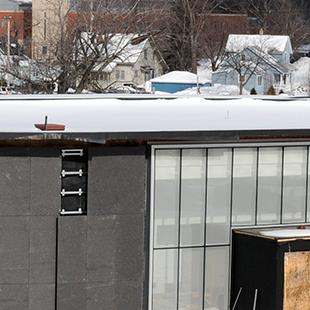 A wide-shot of the construction progress with snow on the ground.