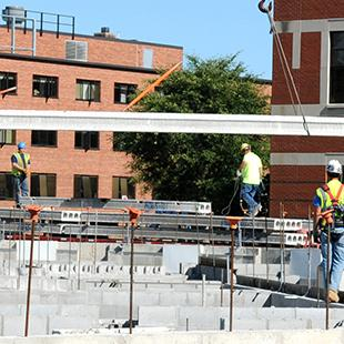 A crane lowering supplies into the construction site with the Martha Miller Center in the background.