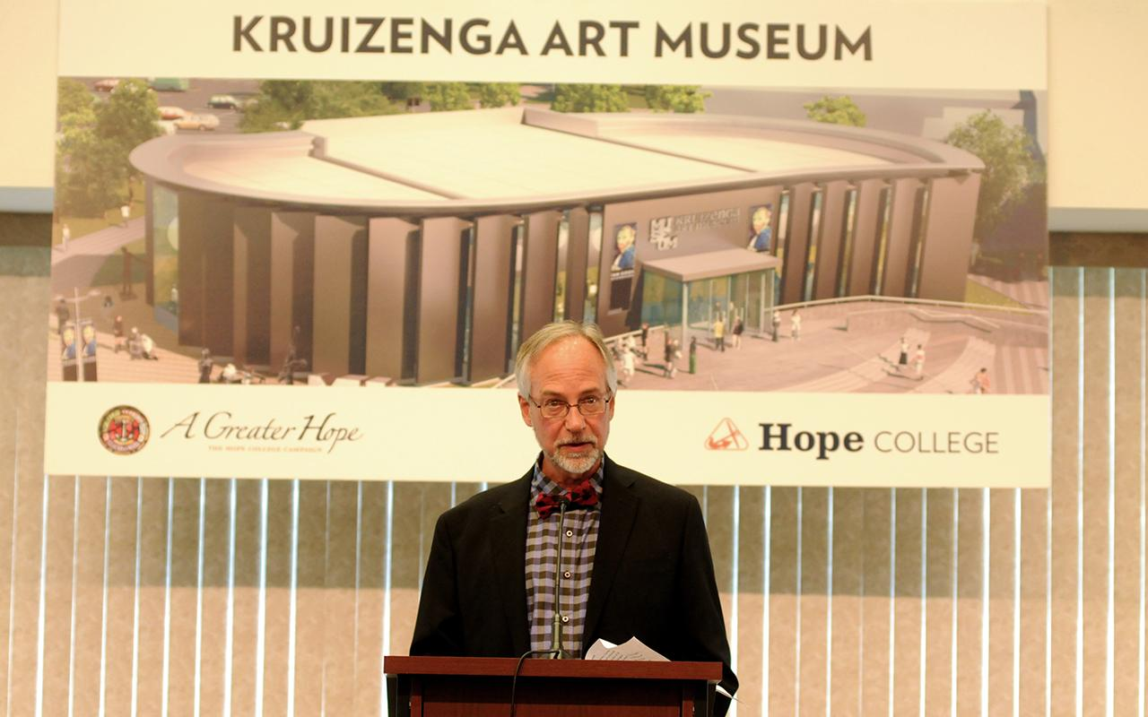 Professor Billy Mayor speaking at a podium in front of a conceptual rendering of the Kruizenga Art Museum.