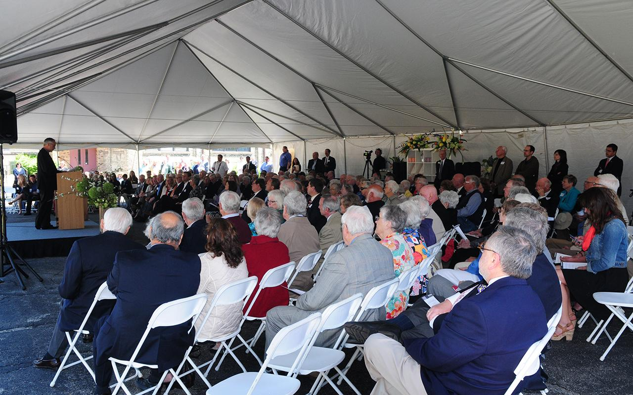 The audience in a tent outside listening to a speaker.