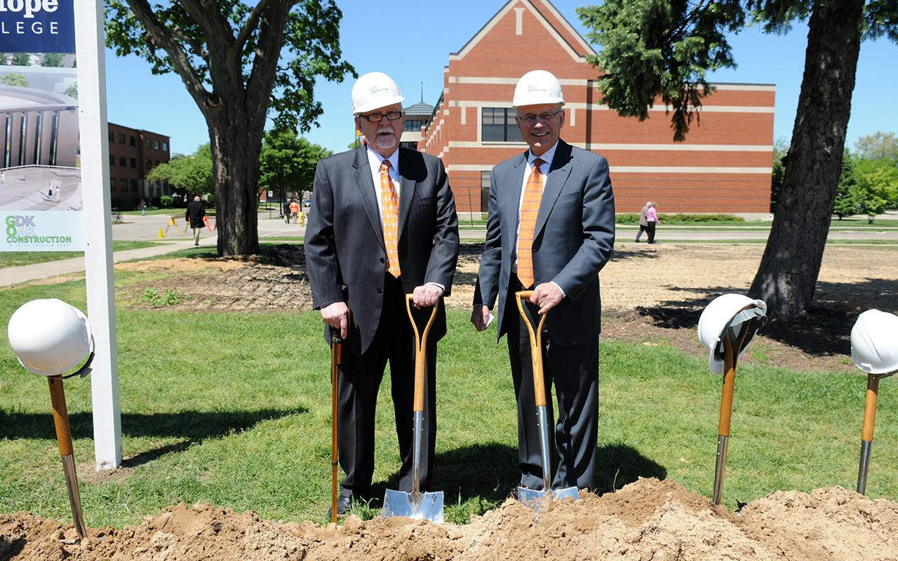 Dr. Richard Kruizenga and President Emeritus James Bultman with hardhats on and shovels in the ground.