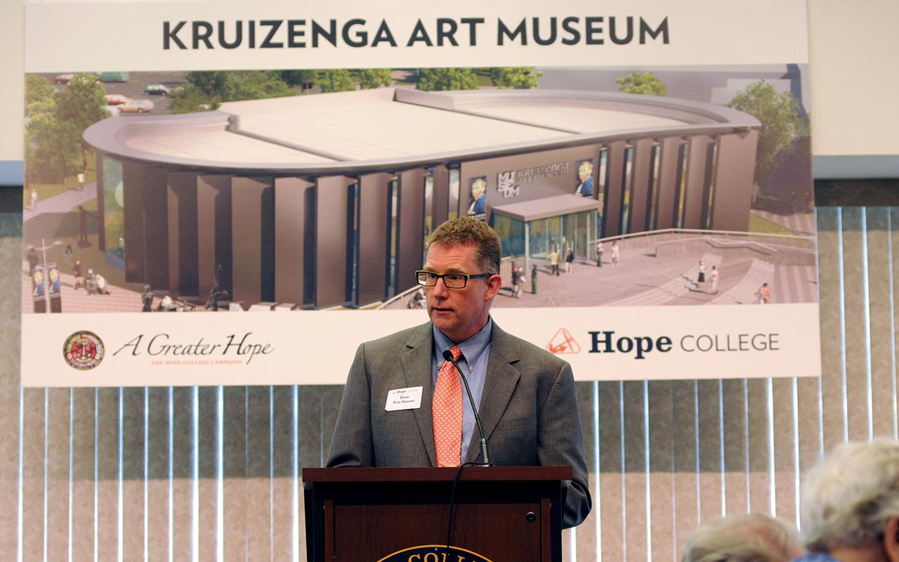 Dana Friis-Hansen, director of the Grand Rapids Art Museum, speaking at a podium in front of a conceptual rendering of the Kruizenga Art Museum.
