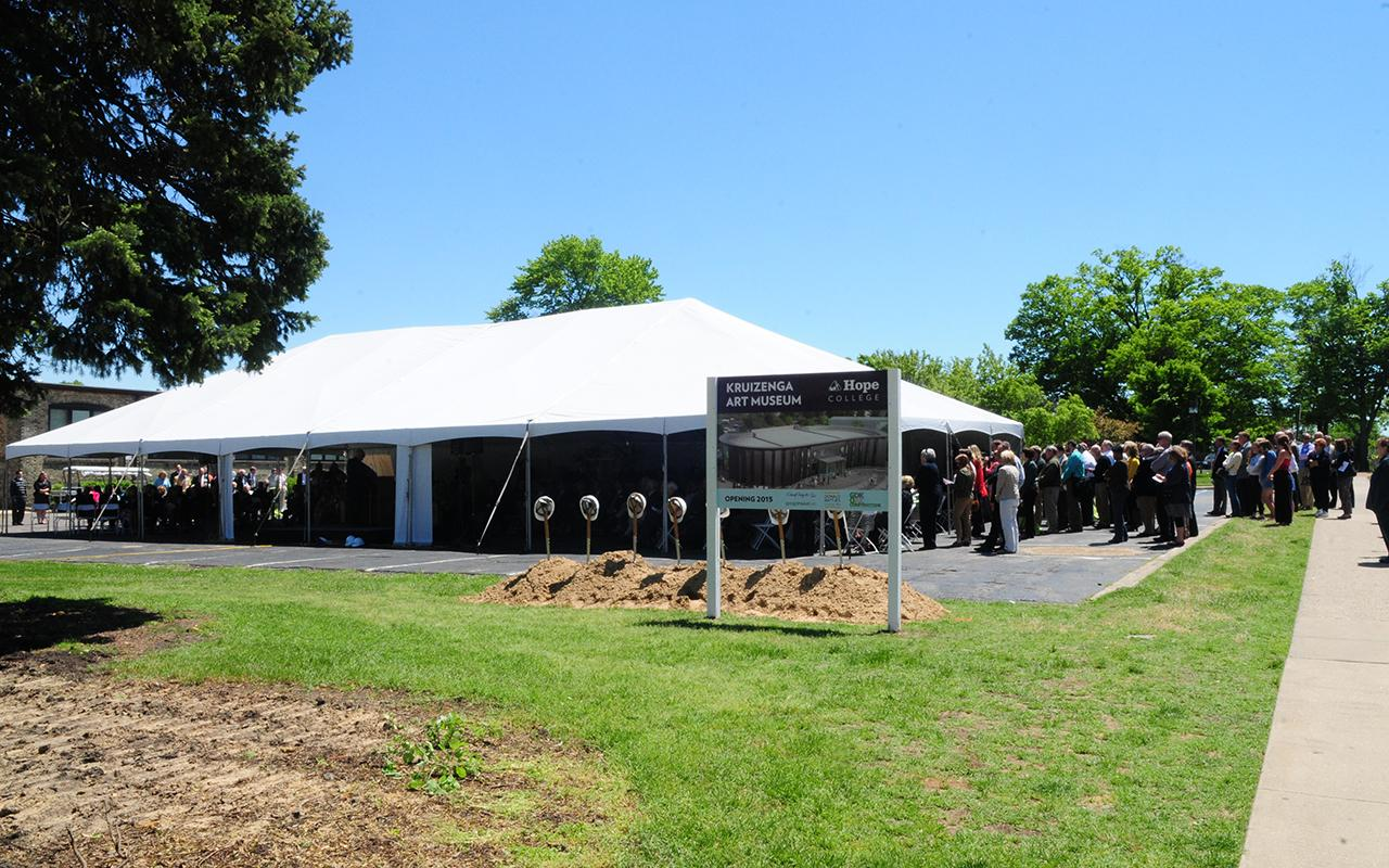 An outdoor tent set up for the groundbreaking with people gathering inside.