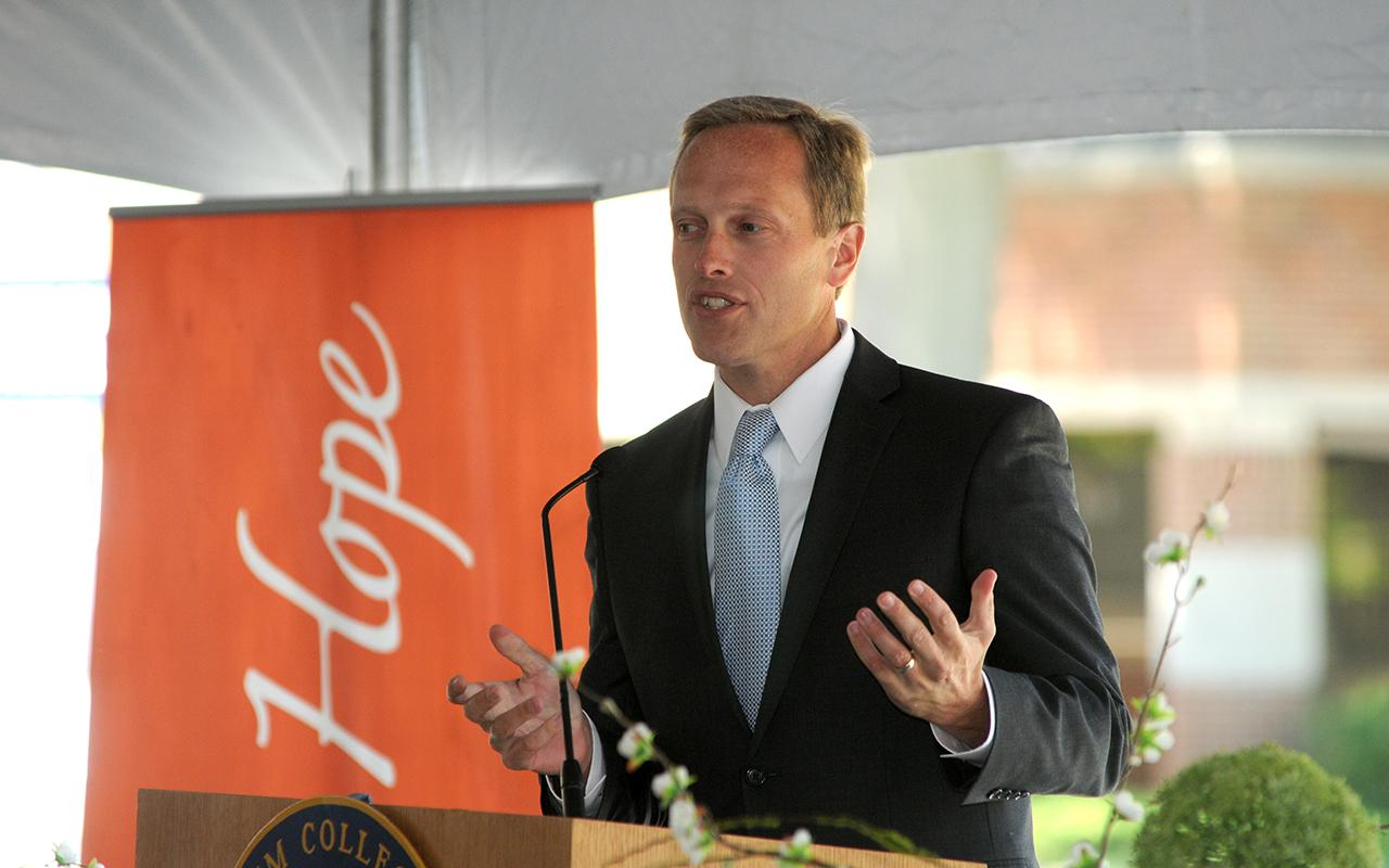 Former Holland, Michigan, mayor Kurt Dykstra speaking at a podium at the groundbreaking ceremony.