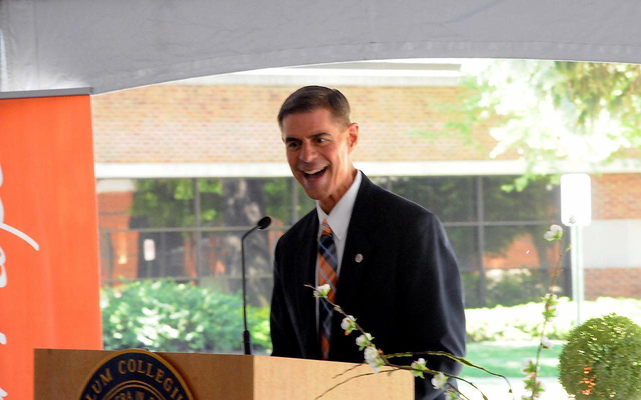 Rev. Bill Boersma speaking at a podium at the groundbreaking.